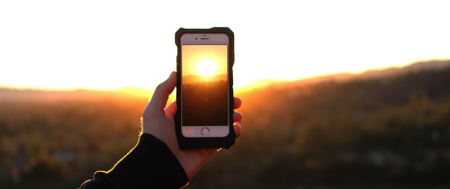 ipower up iPhone Solar charger while hiking at sunset in California